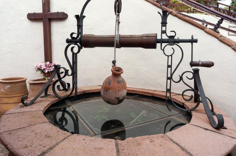 Pozzo spagnolo antico con un saltatore e una brocca dell'argilla su un argano immagine stock