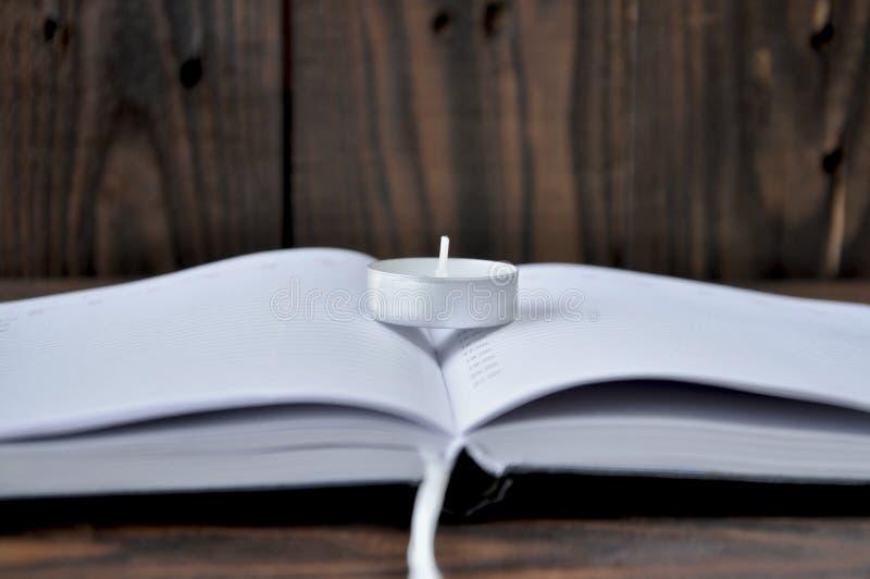 ?ppen bok eller anteckningsbok P? boken ?r en liten stearinljus royaltyfri foto