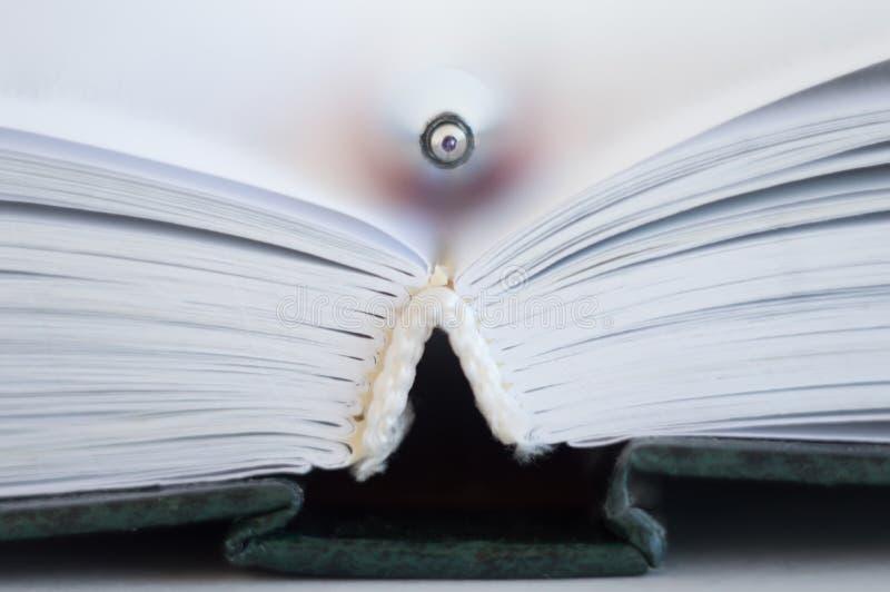 ?ppen bok En penna ligger mellan sidorna i en öppen bok arkivfoto