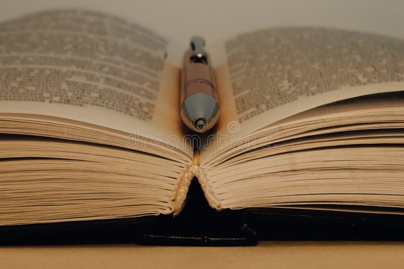 ?ppen bok En penna ligger mellan sidorna i en ?ppen bok royaltyfri fotografi
