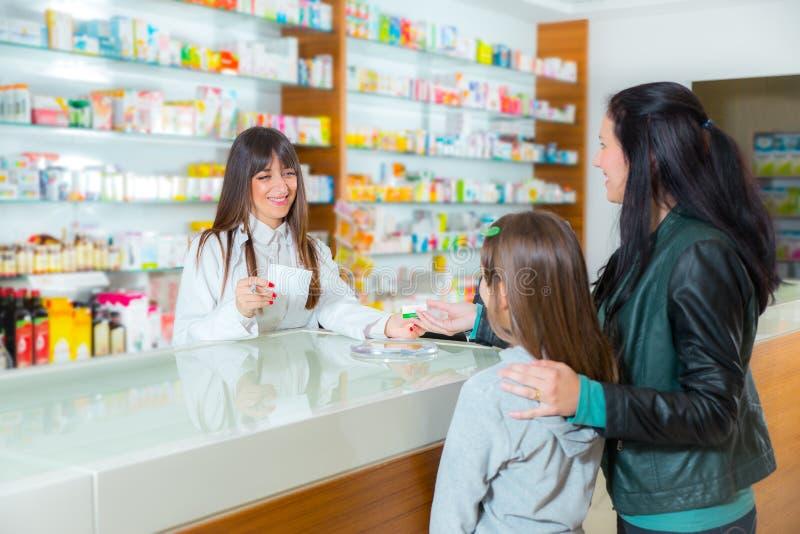 Ppharmacist, das dem Kindermädchen im Apothekendrugstore Vitamine gibt stockfotografie