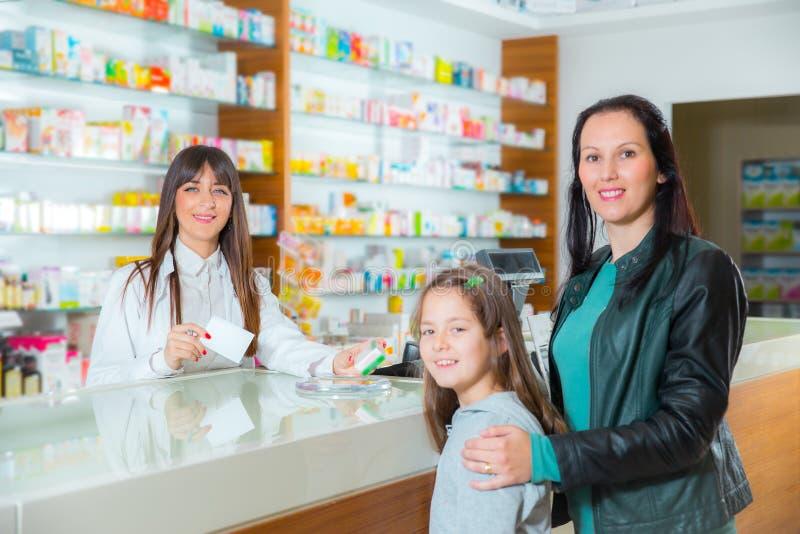 Ppharmacist, das dem Kindermädchen im Apothekendrugstore Vitamine gibt lizenzfreie stockbilder