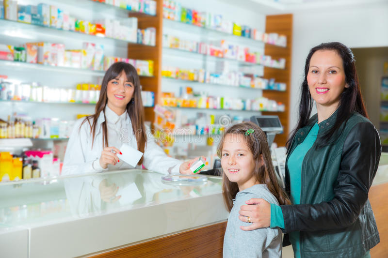 Ppharmacist giving vitamins to child girl in pharmacy drugstore royalty free stock photography
