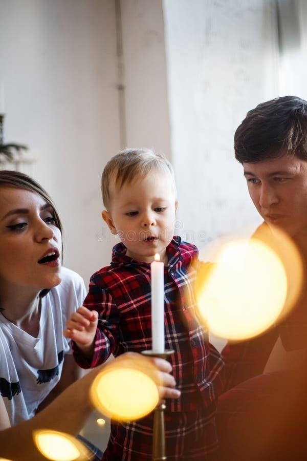 Ppicture vertical de famille L'enfant souffle pour mirer Les parents regardent lui et le sourire photographie stock