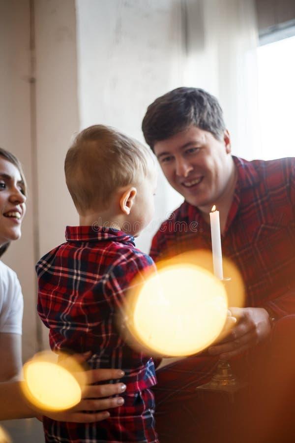 Ppicture vertical de la familia El niño está soplando para mirar al trasluz Los padres están mirando lo y la sonrisa fotografía de archivo
