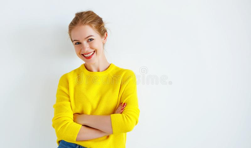 Ppy young woman in yellow sweater on white background. Happy young woman in a yellow sweater on a white background royalty free stock images