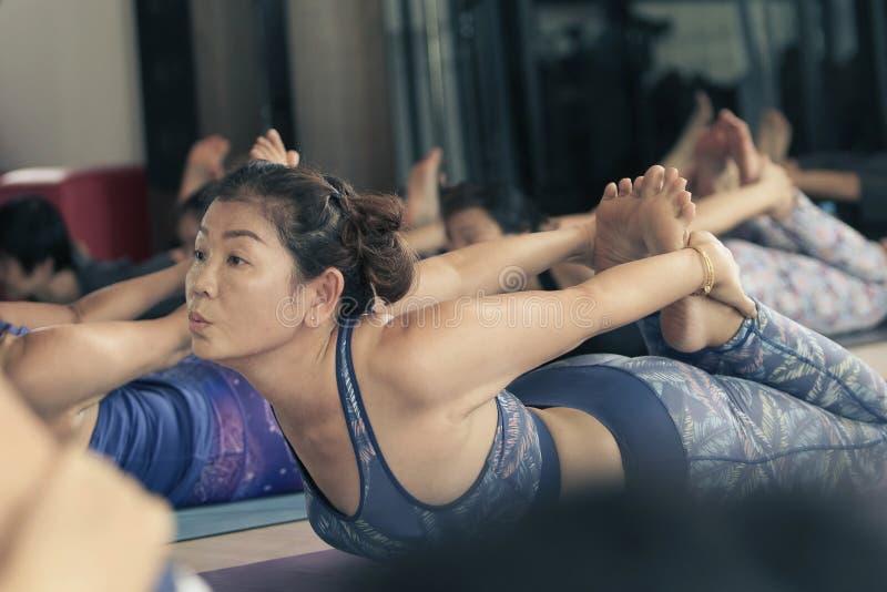 Práctica asiática de la mujer a jugar a yoga foto de archivo
