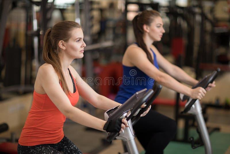 Práctica de la aptitud, hembras hermosas que completan un ciclo en el club de deportes, haciendo ejercicios cardiios fotos de archivo
