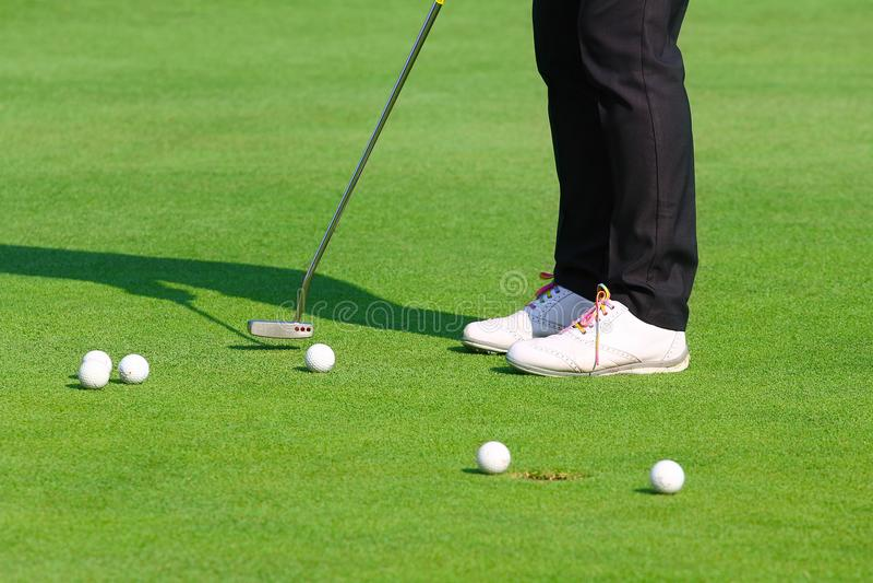Práctica del golfista que pone la pelota de golf en el golf verde, igualando tiempo imagen de archivo libre de regalías
