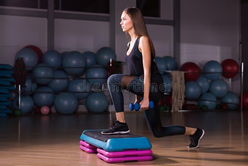 Práctica deportiva de la mujer en la plataforma del paso en gimnasio foto de archivo