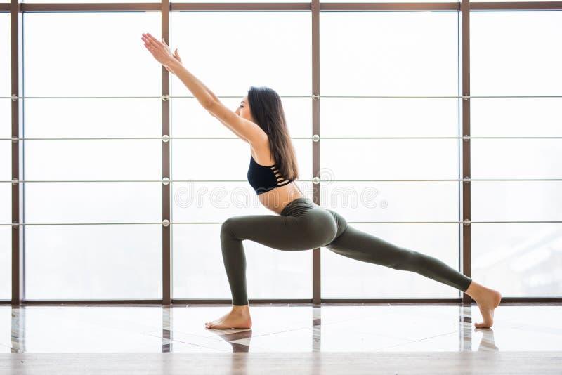 Prática bonita da mulher da ioga de Virabhadrasana perto do fundo do estúdio da sala da ioga da janela Conceito da ioga imagens de stock