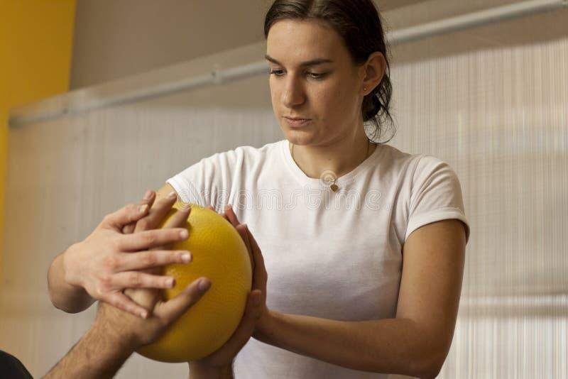 Prática da reabilitação com bola Mãos na bola imagem de stock