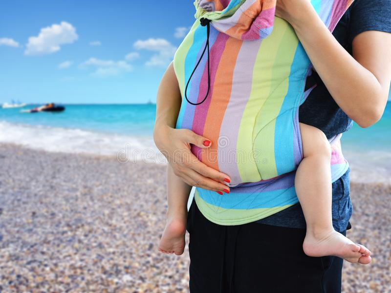 A prática de Babywearing com o bebê levando da mãe no delicado de SSC estruturou o portador no beira-mar fotografia de stock