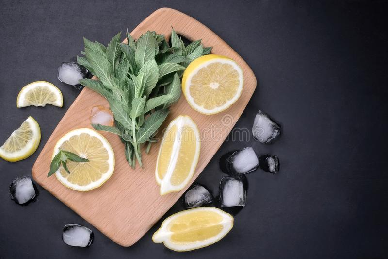 Prägen Sie mit Zitronen- und Eiswürfeln auf einem hölzernen Brett auf einem schwarzen Hintergrund, Draufsicht lizenzfreies stockfoto