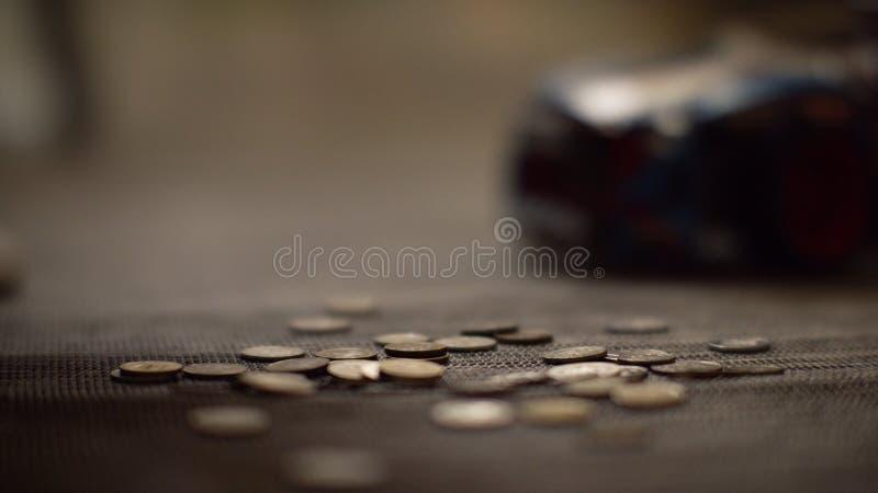 Prägt das Geld, das aus Sparschwein gegossen wird Ei auf goldenem Hintergrund lizenzfreies stockfoto