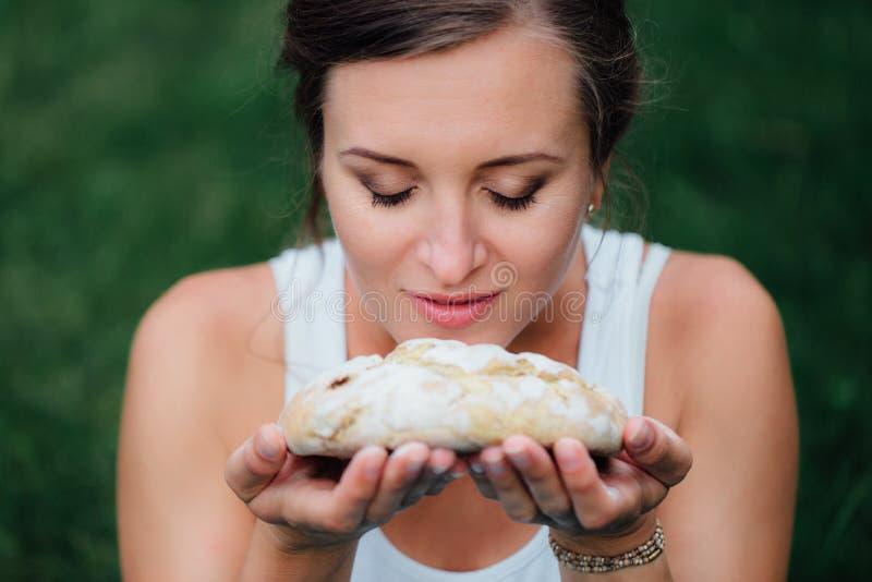 Pränatale Mutterschaft des schwangeren Yoga mit frisch gebackenem selbst gemachtem Brot in den Händen im Park auf dem Gras lizenzfreie stockbilder