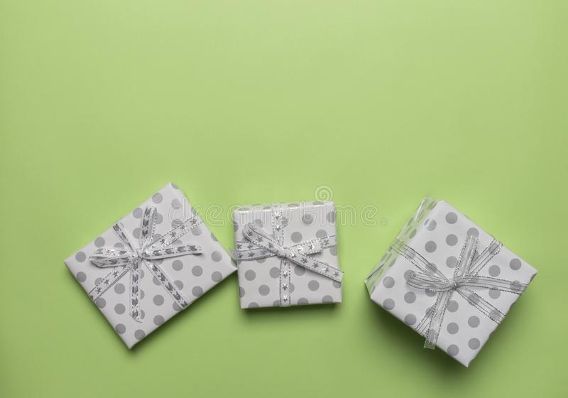 Präsentkartons in den Erbsen mit silbernen Bögen am grünen Hintergrund, Platz für Text lizenzfreie stockfotografie