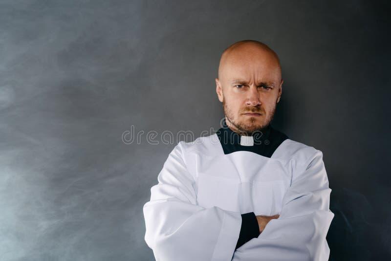 Präst i den vita mässkjortan och svart skjorta med prästmankragen royaltyfria bilder