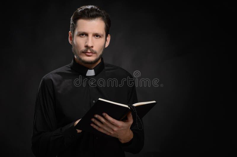 Präst med den heliga bibeln. Stående av prästen som läser den heliga Biblen royaltyfria foton
