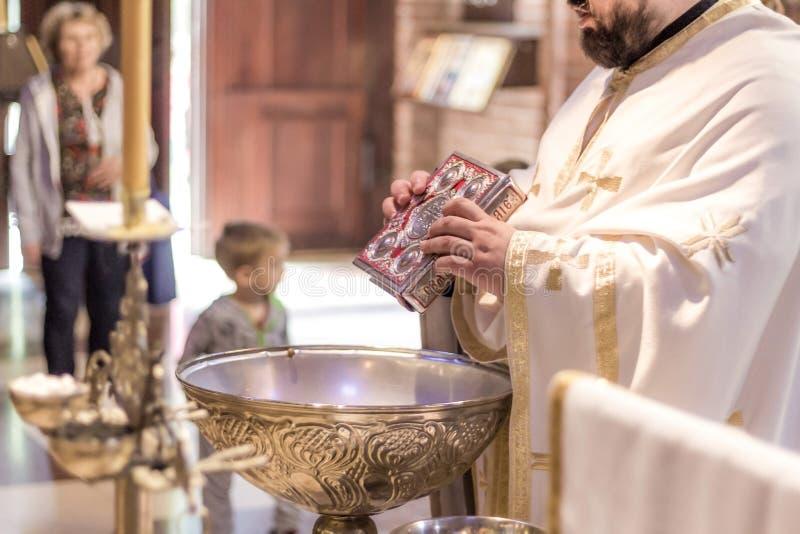 Präst som rymmer den heliga bibeln ovanför det heliga vattnet på ceremonin royaltyfri fotografi