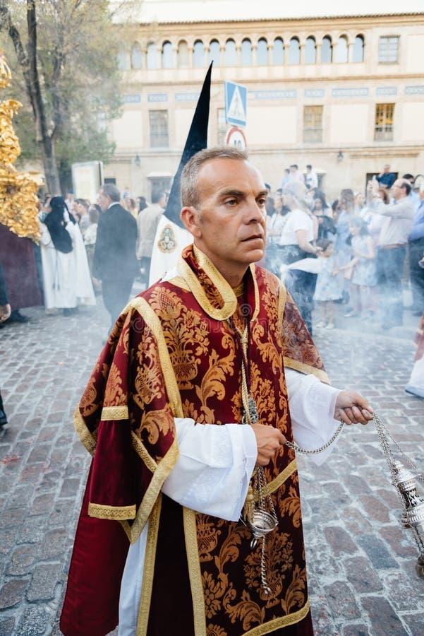 Präst som rymmer en rökelsekar under påskprocession i Cordoba arkivfoto