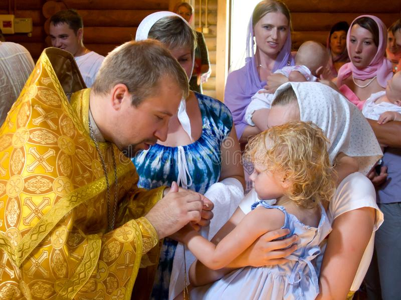 Prästen rymmer ritualen av att smörja barnet efter dop royaltyfria foton