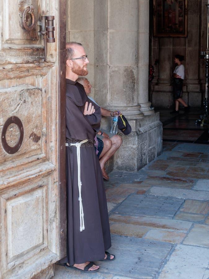 Prästen står benägenhet på dörren på ingången till kyrkan av den heliga griften i den gamla staden av Jerusalem, Israel arkivfoton