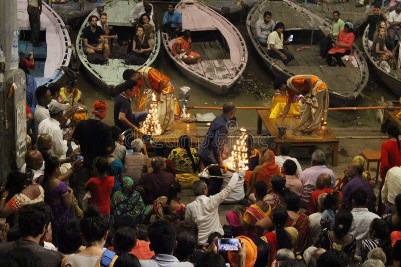 Prästerna dansar med brand som gör ritualen i Varanasi royaltyfri bild