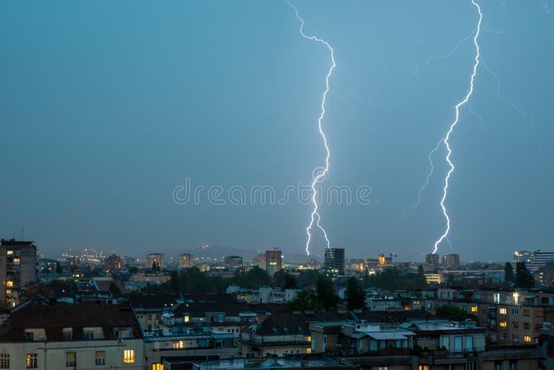 Pråligt slag för blixtåskvigg över stad i natten arkivfoto
