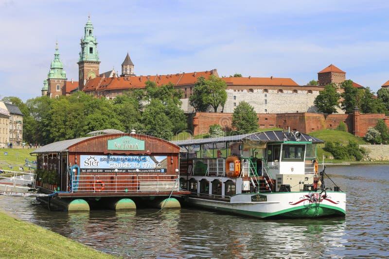 Pråm på den Wisla floden nära Wawel den kungliga slotten i Krakow, Polen royaltyfri fotografi