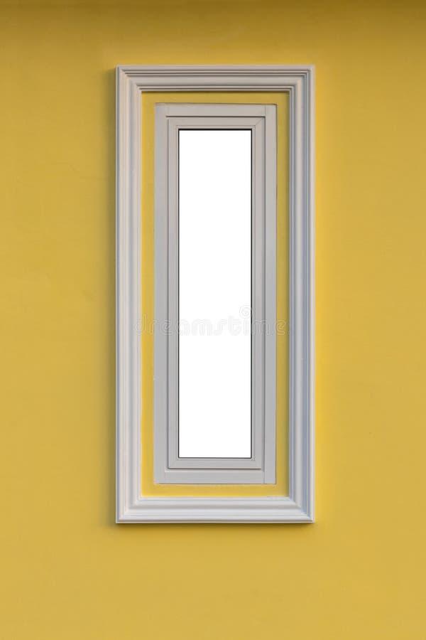 Près de la longue fenêtre blanche sur le mur jaune photographie stock