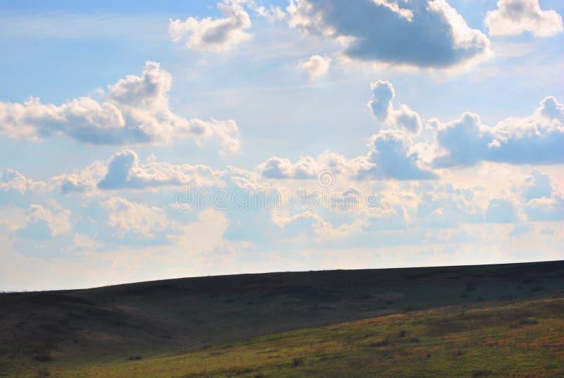 Pré d'herbe sèche sur les collines dans les ombres de soirée, ciel nuageux image stock