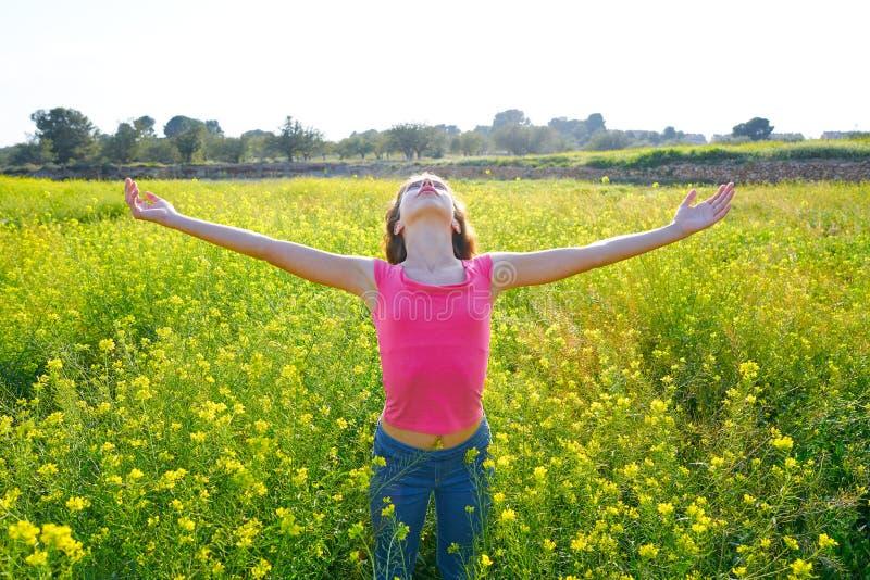 Pré de l'adolescence heureux de fille de bras ouverts au printemps photographie stock