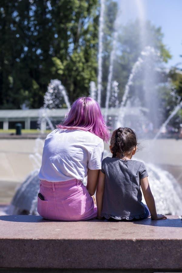 Préadolescent élégant s'asseyant avec la fontaine de observation d'enfant photos libres de droits