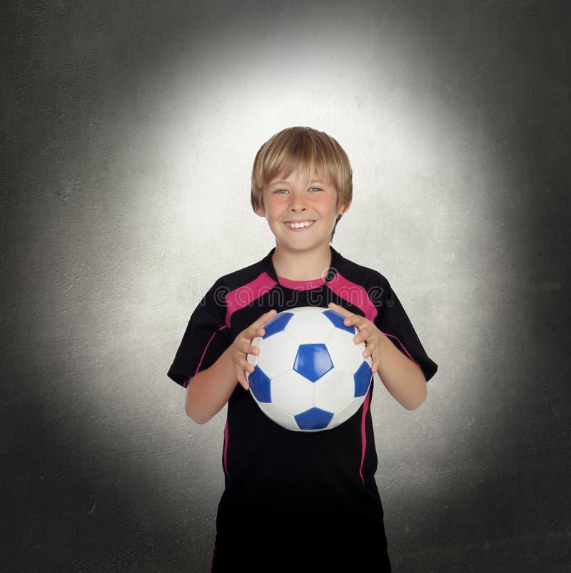 Préadolescent avec un uniforme pour le football de jeu images stock