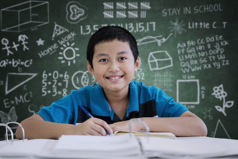 Préadolescent beau faisant des notes dans la salle de classe photo stock