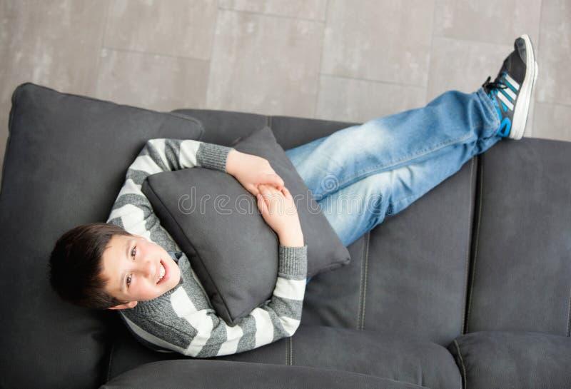 Préadolescent de sourire sur le sofa à la maison photo libre de droits