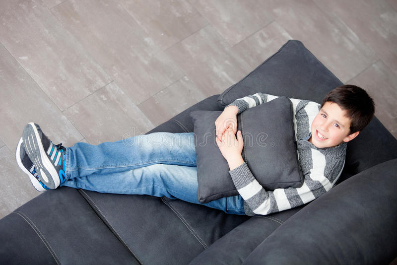 Préadolescent de sourire sur le sofa à la maison photos stock
