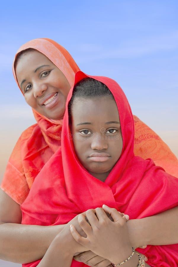 Préadolescent rebelle dans les bras de sa mère photographie stock