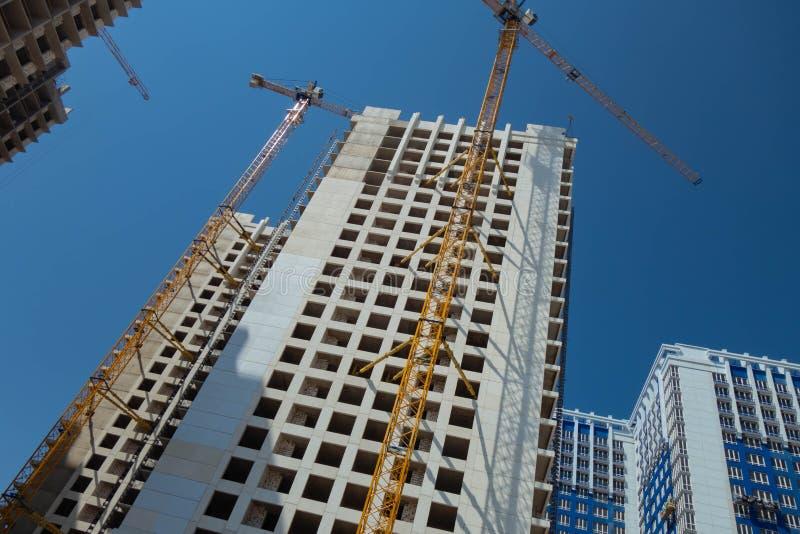 Prédio branco sob guindastes da construção e de torre contra o céu azul foto de stock royalty free