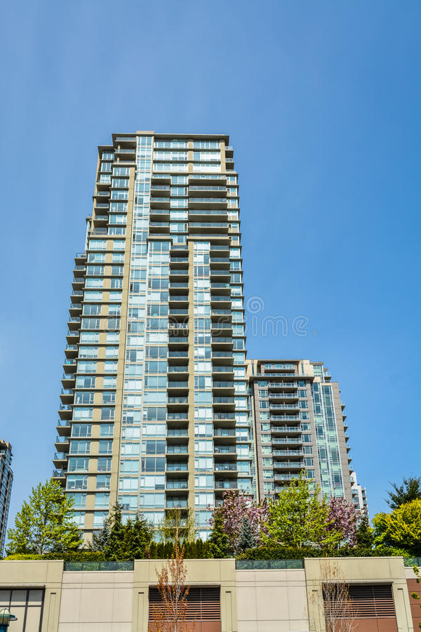 Prédio de apartamentos alto da elevação em Vancôver no fundo do céu azul imagens de stock