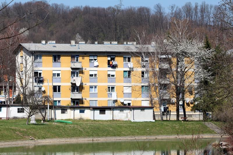 Prédio de apartamentos amarelo velho pequeno com as garagens velhas na parte dianteira cercada com grama verde e vegetação de flo fotos de stock royalty free
