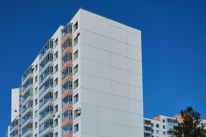Prédio de apartamentos moderno dos blocos de cimento com um fundo profundo do céu azul fotografia de stock