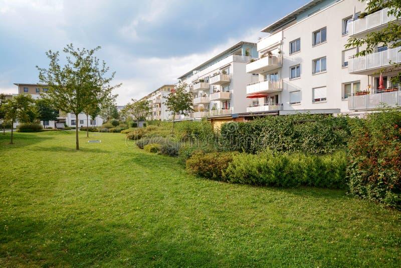 Prédio de apartamentos novo, desenvolvimento residencial moderno com facilidades exteriores em um pagamento urbano verde fotos de stock royalty free