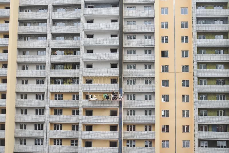 Prédio de apartamentos novo sob a construção Os construtores emplastram paredes fotografia de stock
