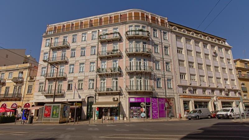 Prédio de apartamentos típico na cor pastel cor-de-rosa com as lojas no nível da rua em Lisboa, Portugal fotos de stock royalty free