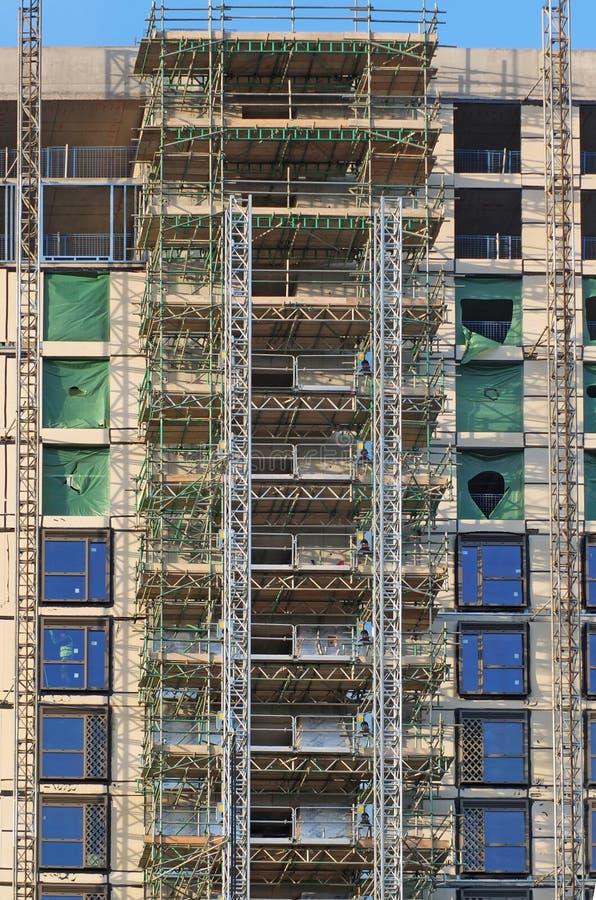 prédio de apartamentos de vários andares moderno alto sob a construção com quadros do andaime e da grua sob um céu azul imagens de stock royalty free