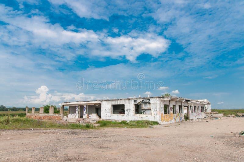 Prédio de escritórios abandonado com o céu azul bonito, anti slogan do governo nas paredes imagem de stock royalty free