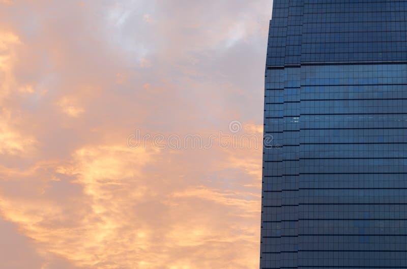 Prédio de escritórios azul das janelas de vidro com céu da manhã imagem de stock