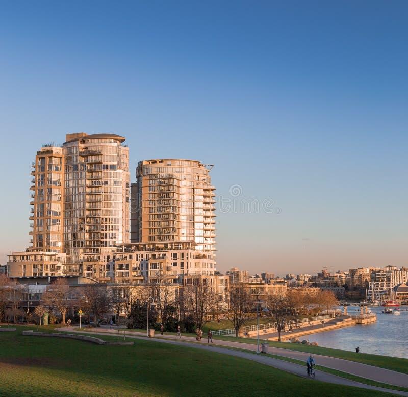 Prédios de apartamentos ao lado de False Creek, Vancôver, no por do sol fotos de stock